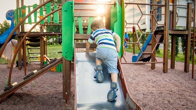 Afbeelding van een gelukkig lachende vrolijke peuterjongen die rijdt en klimt op de grote kinderspeelplaats in het park