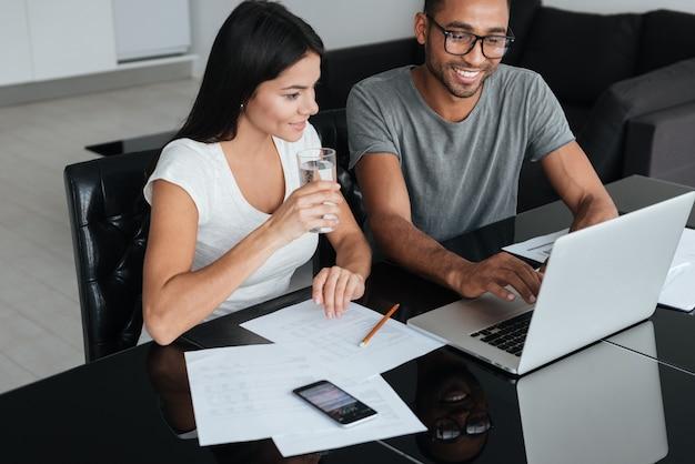 Afbeelding van een gelukkig liefdevol jong stel dat laptop gebruikt en hun financiën analyseert met documenten. kijk naar laptop.