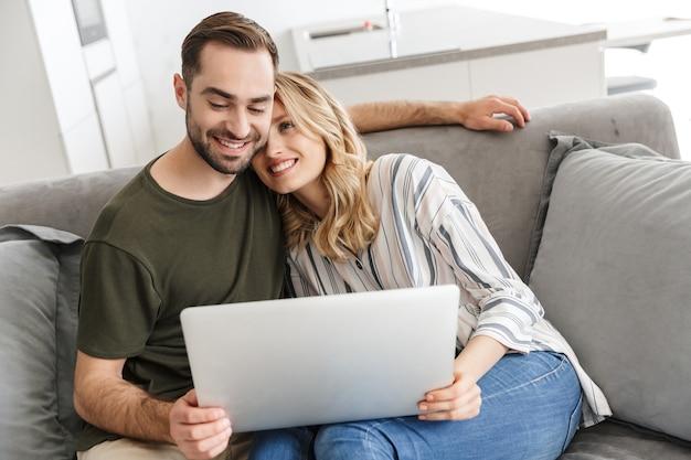 Afbeelding van een gelukkig opgewonden jong verliefd stel dat thuis op de bank zit met een laptopcomputer.