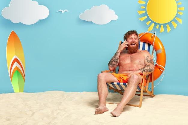 Afbeelding van een gelukkig roodharige man in korte broek blij om een telefoongesprek te hebben met een vriend, heeft een rode zonverbrande huid