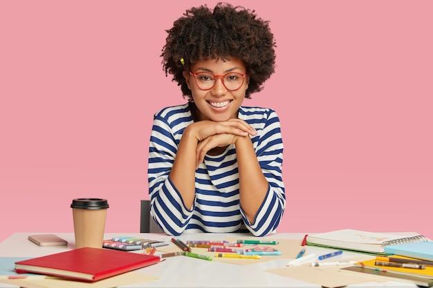 Afbeelding van een gelukkig tienermeisje met brede glimlach, houdt de handen onder de kin, verheugt zich over positieve opmerkingen over haar werk
