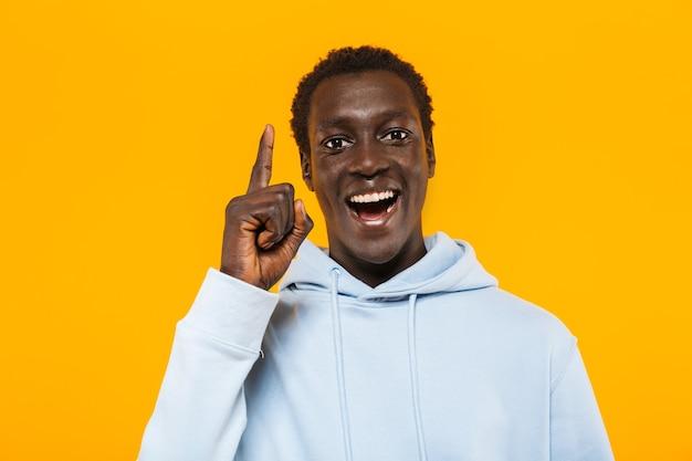 Afbeelding van een gelukkige afro-amerikaanse man in streetwear-hoodie die lacht en met de vinger naar boven wijst als ideeteken Premium Foto