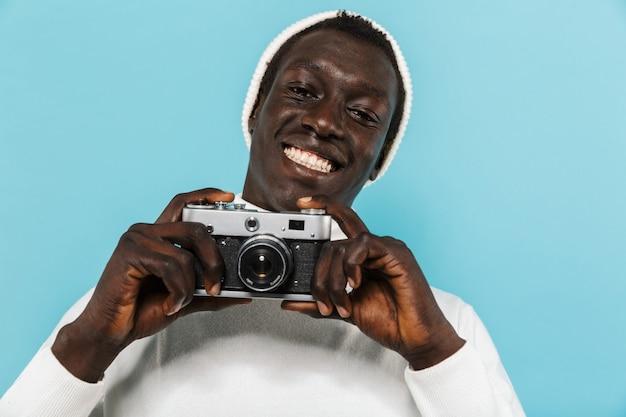 Afbeelding van een gelukkige afro-amerikaanse man in witte kleren die lacht en fotografeert op retro camera