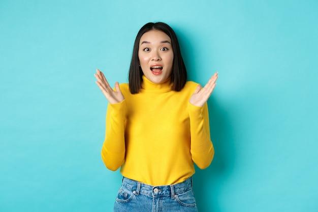 Afbeelding van een gelukkige aziatische vrouw klapt in de handen en kijkt verbaasd, staande in gele trui op blauwe achtergrond