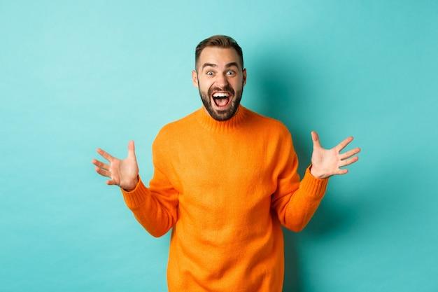 Afbeelding van een gelukkige en opgewonden man kondigt groot nieuws aan, spreidt zijn handen uit en schreeuwt van vreugde, verheugt zich over de licht turkooizen muur.