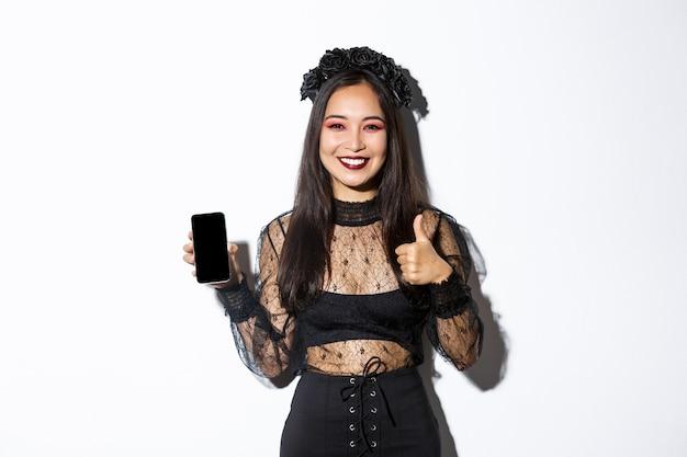 Afbeelding van een gelukkige en tevreden aziatische vrouw in halloween-kostuum met thumbs-up en demonstrerende gsm-scherm, glimlachend blij, staande op witte achtergrond.