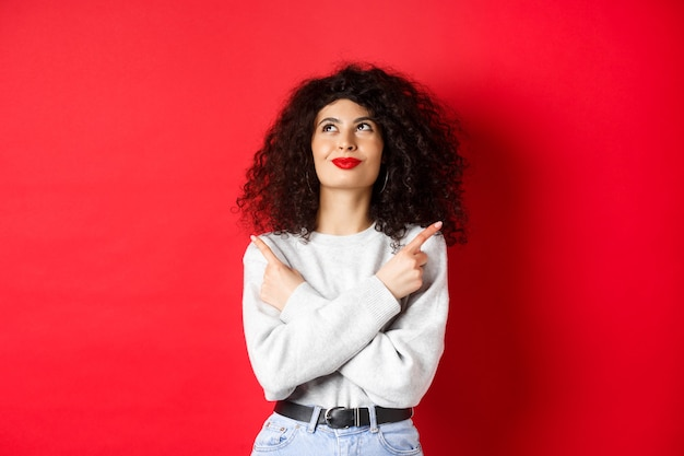 Afbeelding van een gelukkige glimlachende vrouw die zijwaarts wijst, met vastberaden gezicht opkijkt, iets kiest, zelfverzekerd staat in haar beslissing op rode achtergrond