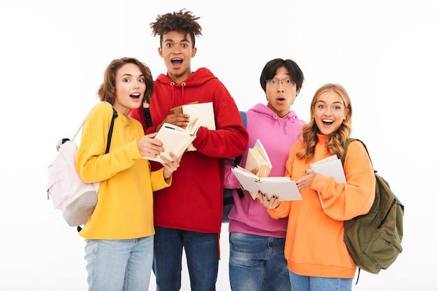 Afbeelding van een gelukkige jonge groep vrienden studenten geïsoleerd staan, poseren.