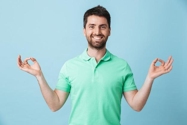 Afbeelding van een gelukkige jonge, knappe, bebaarde man die zich voordeed over een blauwe muur met een goed gebaar om te mediteren.