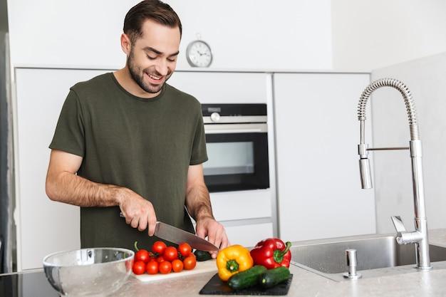 Afbeelding van een gelukkige jonge knappe man die thuis in de keuken kookt, ontbijten.