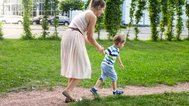 Afbeelding van een gelukkige jonge moeder met een zoontje van 3 jaar dat speelt en rent op de kinderspeelplaats in het park