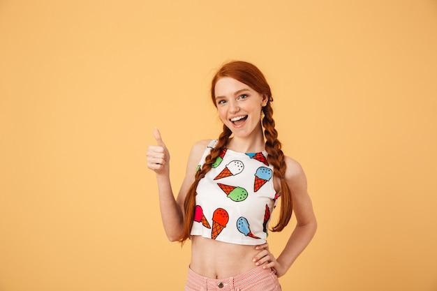 Afbeelding van een gelukkige jonge mooie roodharige vrouw gekleed in een met ijs bedrukt t-shirt poseren geïsoleerd over gele muur met duimen omhoog gebaar.