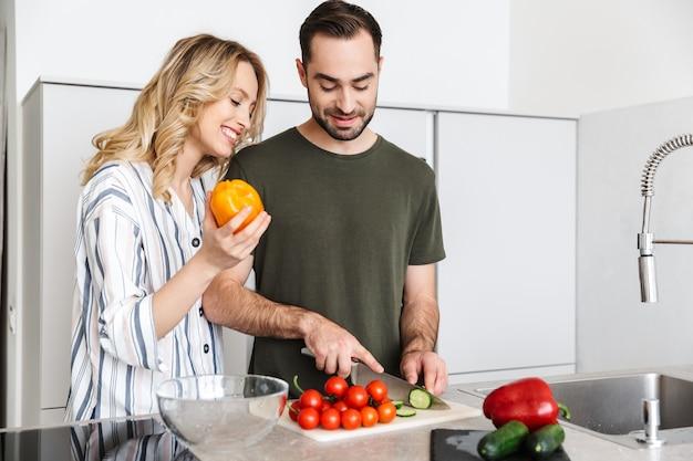 Afbeelding van een gelukkige jonge verliefde paar poseren in de keuken thuis koken ontbijten.