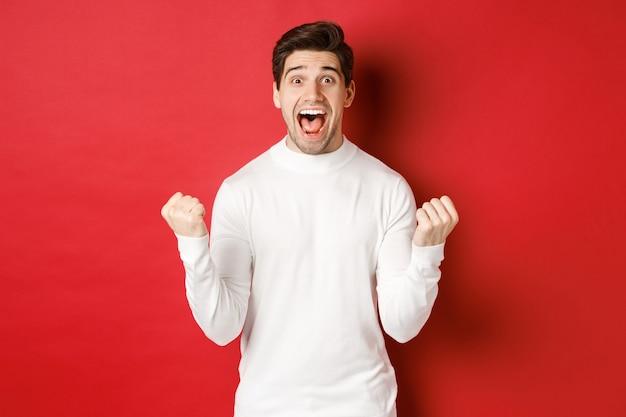 Afbeelding van een gelukkige knappe man in een witte trui die iets wint en een vuistpomp maakt en glimlacht, verbazen...