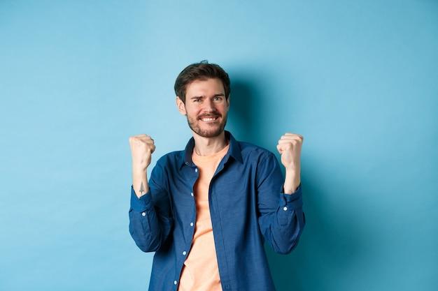 Afbeelding van een gelukkige man die succes viert, ja schreeuwt en gebalde vuisten schudt, doel bereikt en triomfeert, wint en dansen, staande op blauwe achtergrond.