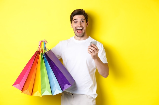 Afbeelding van een gelukkige man ontvangt cashback voor aankoop, houdt smartphone en boodschappentassen vast, glimlachend opgewonden, staande op gele achtergrond.