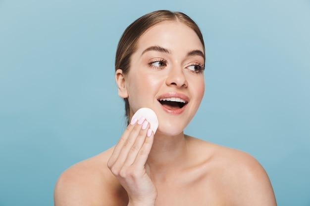 Afbeelding van een gelukkige mooie jonge vrouw zorgt voor haar huid geïsoleerd over blauwe muur met wattenschijfje.