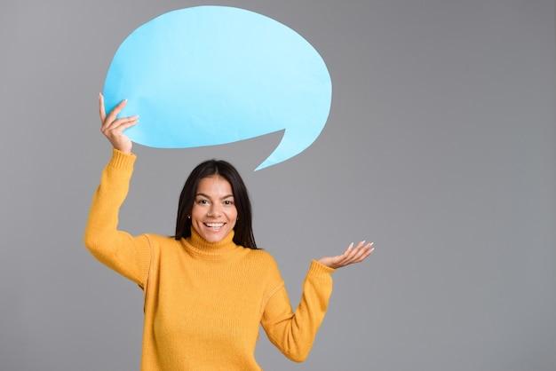 Afbeelding van een gelukkige vrouw poseren geïsoleerd over grijze muur met tekstballon.