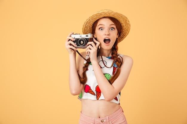 Afbeelding van een geschokte jonge mooie roodharige vrouw fotograaf toerist gekleed in ijs bedrukt t-shirt poseren geïsoleerd over gele muur met camera.