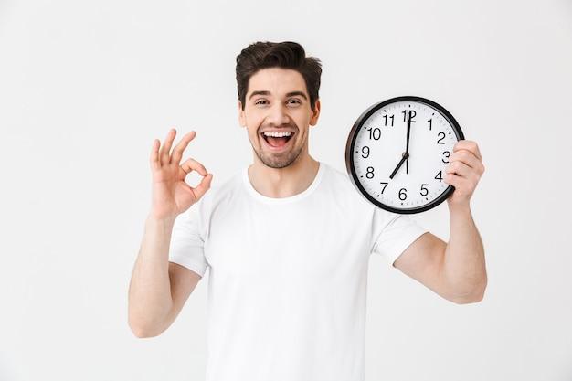Afbeelding van een geschokte opgewonden gelukkige jonge man die zich voordeed over een witte muur met een klok die een goed gebaar toont.