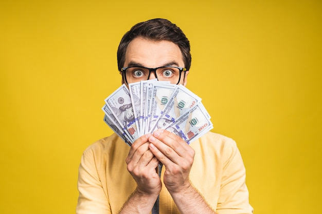 Afbeelding van een geschokte opgewonden jonge knappe bebaarde man die zich voordeed op een gele muurachtergrond die geld vasthoudt, maakt een winnaargebaar.