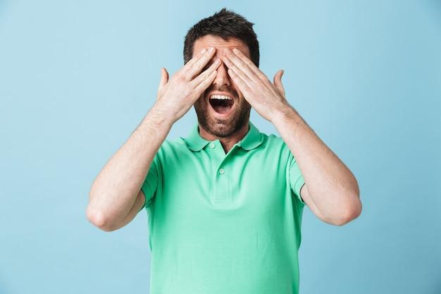 Afbeelding van een geschokte opgewonden jonge knappe bebaarde man die zich voordeed over blauwe muur die ogen bedekt met handen.