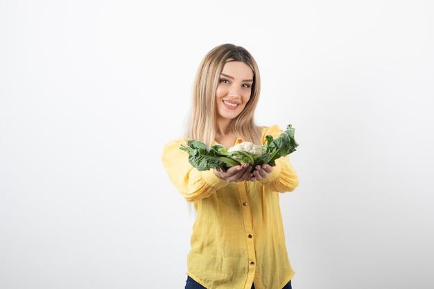 Afbeelding van een glimlachend mooi vrouwenmodel dat bloemkool vasthoudt.