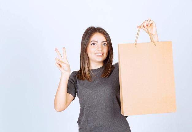 Afbeelding van een glimlachende vrouw die een papieren zak vasthoudt en een overwinningsteken toont.