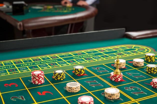 Afbeelding van een groene tafel en wedden met chips. detailopname
