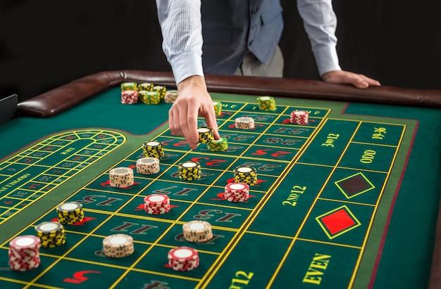Afbeelding van een groene tafel en wedden met chips. man overhandigen casinofiches op roulettetafel. detailopname