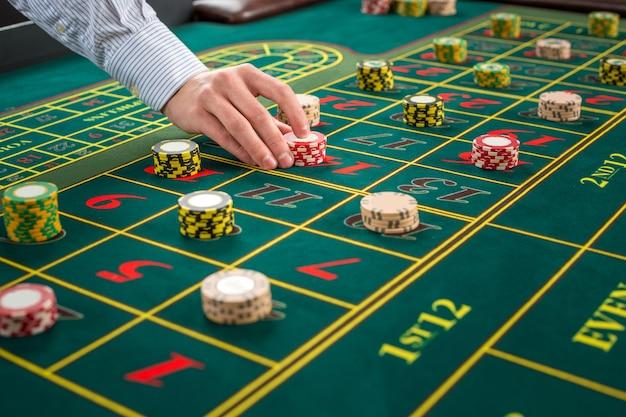 Afbeelding van een groene tafel en wedden met chips