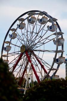 Afbeelding van een groot rood reuzenrad met achtergrondverlichting tegen een wazige lichtblauwe lucht