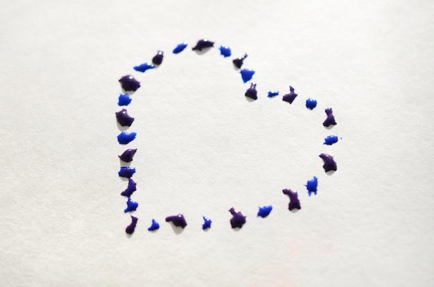 Afbeelding van een hart gemaakt van natte druppels waterverf op een vel papier