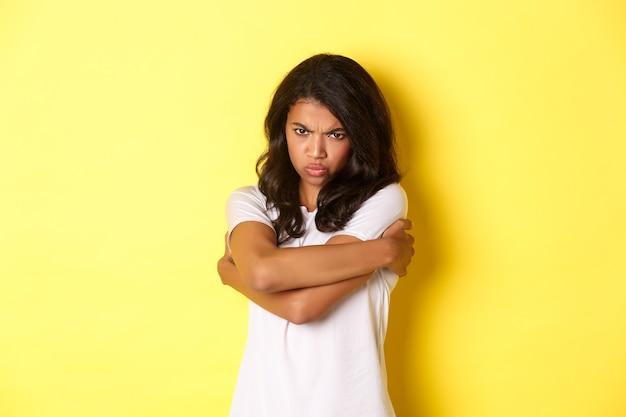 Afbeelding van een humeurig schattig afro-amerikaans meisje, zichzelf knuffelend en mokkend met een beledigde uitdrukking, staande op een gele achtergrond.