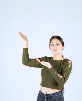 Afbeelding van een jong glimlachend vrouwenmodel dat met handen omhoog wijst.