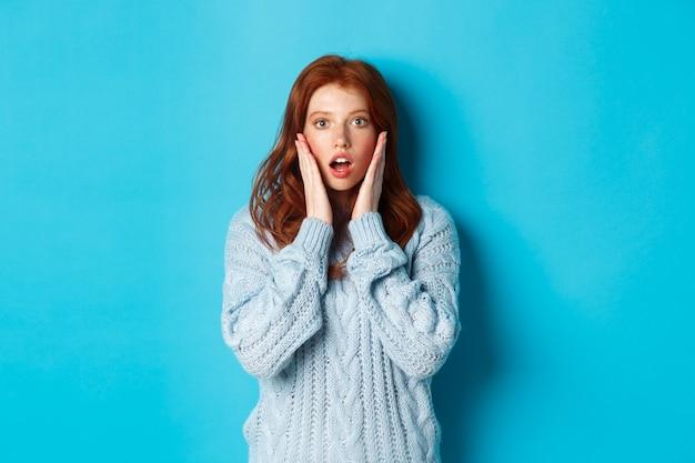 Afbeelding van een jong mooi roodharig meisje, verbaasd kijkend, starend met volledig ongeloof naar de camera, staand in trui tegen blauwe achtergrond