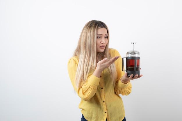 Afbeelding van een jong mooi vrouwenmodel dat een theepot houdt.