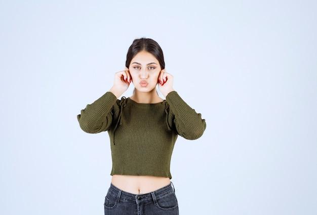 Afbeelding van een jong mooi vrouwenmodel dat oorlellen met vingers vasthoudt.