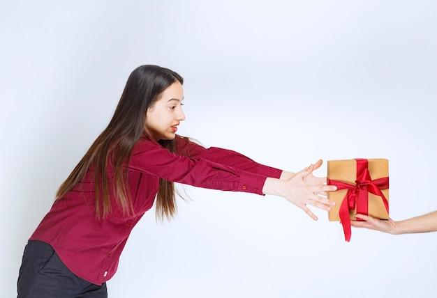 Afbeelding van een jong vrouwenmodel dat een cadeautje met strik op een witte muur neemt.