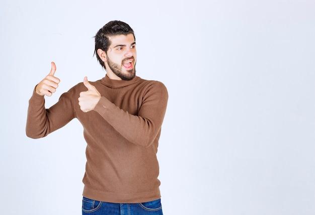 Afbeelding van een jonge, aantrekkelijke man gekleed in een bruine trui die op een witte achtergrond staat en een gebaar toont