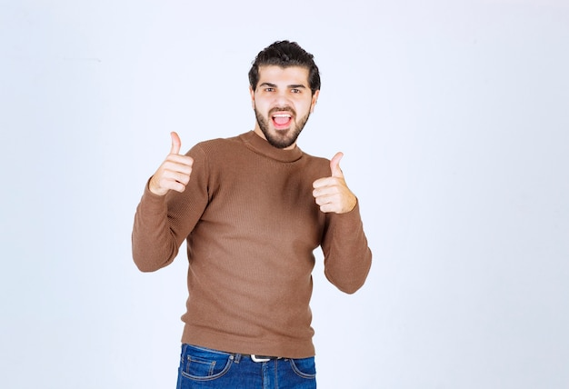 Afbeelding van een jonge aantrekkelijke man gekleed in een bruine trui die over een witte achtergrond staat en naar de camera kijkt en een duim omhoog gebaar toont. hoge kwaliteit foto