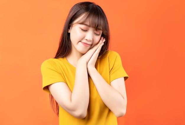 Afbeelding van een jonge aziatische vrouw, gekleed in geel t-shirt op oranje