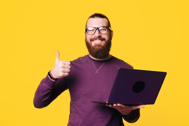 Afbeelding van een jonge bebaarde man houdt een computer met een duim omhoog lacht