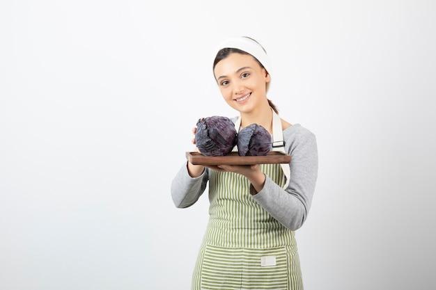 Afbeelding van een jonge glimlachende huisvrouw die een bord paarse kool vasthoudt