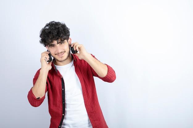 Afbeelding van een jonge kerel in koptelefoon camera kijken op witte achtergrond. hoge kwaliteit foto