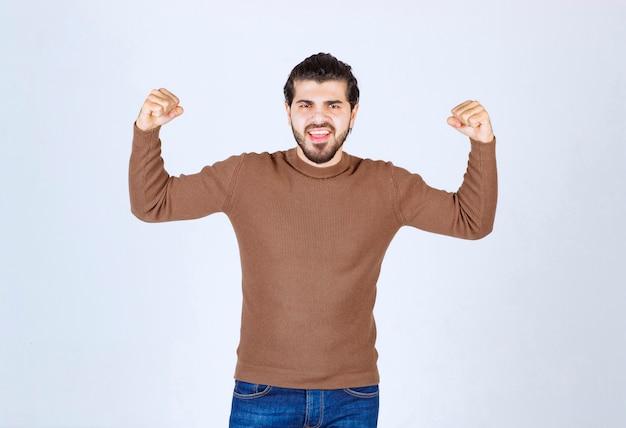 Afbeelding van een jonge knappe man die staat en zijn spieren laat zien. hoge kwaliteit foto