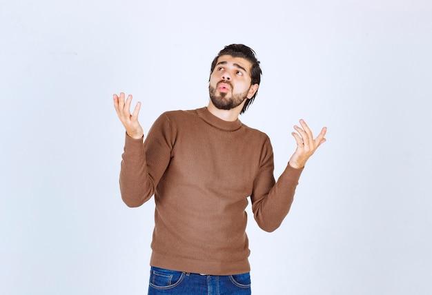Afbeelding van een jonge knappe man model staand en verrassend opkijkend. hoge kwaliteit foto