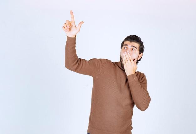 Afbeelding van een jonge knappe man model staande en omhoog met de vingers. hoge kwaliteit foto