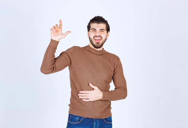 Afbeelding van een jonge lachende man model staan en omhoog wijzend met een wijsvinger. hoge kwaliteit foto