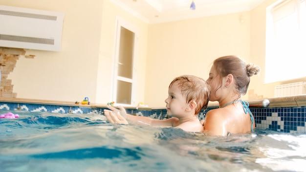 Afbeelding van een jonge moeder die haar kleine 3-jarige jongenskind leert zwemmen en met een kleurrijke strandbal speelt in het binnenzwembad indoor
